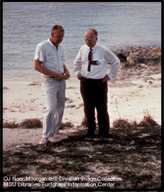 O.J. Noer and another man standing on beach looking at grass